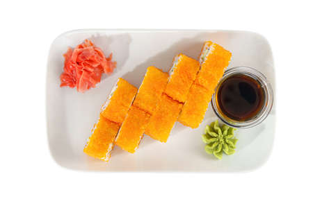 Sushi, rolls, uramaki california with tobiko caviar, avocado, raw seafood, soy sauce, marinated ginger and wasabi, white isolated background, view from above Imagens