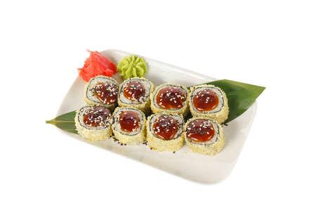 Sushi, rolls, uramaki, tempura with teriyaki sauce, sesame, raw seafood, marinated ginger and wasabi. Food on a banana leaf, on plate, white isolated background, side view Imagens