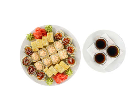 Set of sushi for a large company, rolls, california, philadelphia with lava sauce, marinated ginger, soy sauce and wasabi, white isolated background, side view