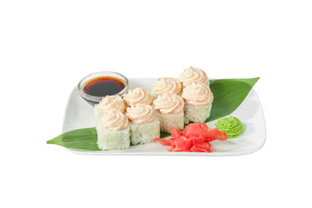 Sushi, rolls, uramaki, alaska with lava sauce, tobiko caviar, raw seafood, soy sauce, marinated ginger and wasabi. Food on a banana leaf, on plate, white isolated background, side view