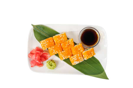 Sushi, rolls, uramaki california with tobiko caviar, avocado, raw seafood, soy sauce, marinated ginger and wasabi on a banana leaf, white isolated background, view from above