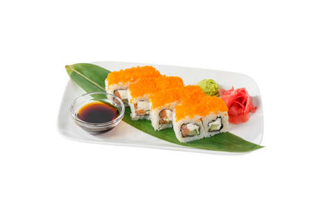 Sushi, rolls, uramaki california with tobiko caviar, cucumber, cheese, crab meat, raw seafood, soy sauce, marinated ginger and wasabi on a banana leaf, on plate, white isolated background, side view