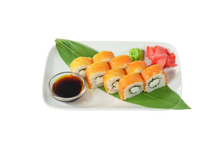 Sushi, rolls, uramaki, philadelphia with salmon, crab meat, cheese, raw seafood, soy sauce, marinated ginger and wasabi. Food on a banana leaf, on plate, white isolated background, side view
