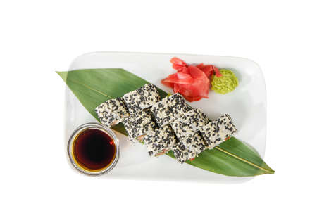 Sushi, rolls, uramaki with sesame, avocado, cucumber, cheese and salmon, fish, raw seafood, soy sauce, marinated ginger and wasabi. Food on a banana leaf, white isolated background, view from above