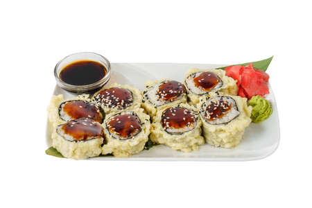 Sushi, rolls, uramaki, tempura with teriyaki sauce, sesame, raw seafood, soy sauce, marinated ginger and wasabi. Food on a banana leaf, on plate, white isolated background, side view