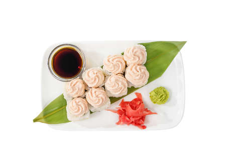 Sushi, rolls, uramaki, alaska, with lava sauce, tobiko caviar, raw seafood, soy sauce, marinated ginger and wasabi. Food on a banana leaf, on plate, white isolated background, view from above