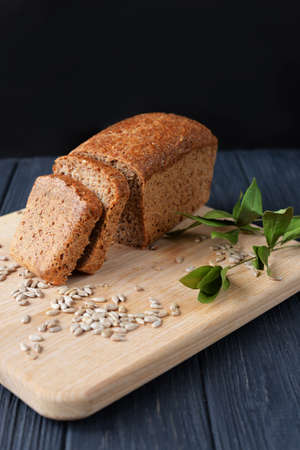 aromatic meal baking bread from dough on a wooden board on a beautiful background with plant leaves with sunflower seeds