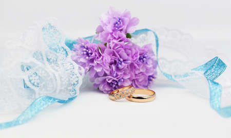 gold wedding engagement rings with white ribbons lace lilac flowers on a white background