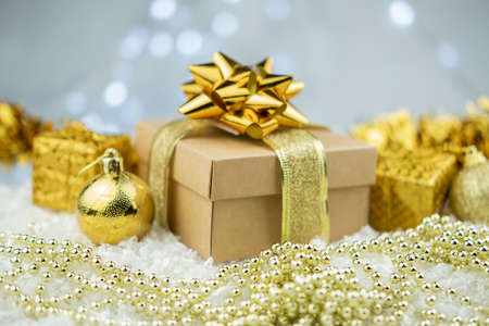 gift boxes packing with a bow and ribbon of gold color and decorations with toys balls on the snow on a bokeh background for the new year