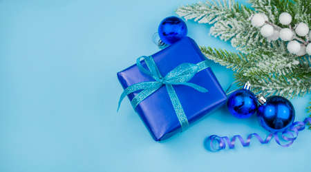 beautiful christmas gift box with a blue bow wirh  snow on a blue background for valentine's holiday decorations and a christmas tree