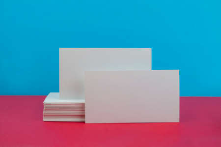 white mockup for business cards for designe  on a blue and pink background
