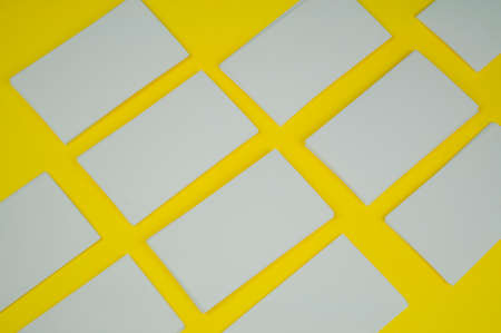 many blank white mokap business cards on a yellow background