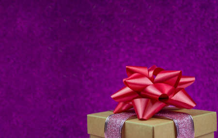 surprise gift with red bow on bokeh background for winter holiday new year and valentine's day Stockfoto