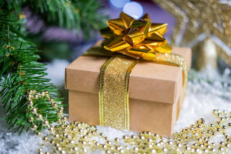gift boxes packing with a bow and ribbon in gold color on the snow on a bokeh background for the new year