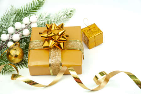 gift boxes packing with a bow and ribbon of gold color and decorations with ornament  balls on a bokeh background for the new year