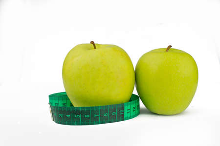 green apples with measuring centimeter for weight control and health and diet on a white background