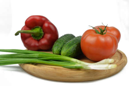 board on a wooden board vegetables with green onions tomatoes red paprika peppers green cucumbers and diet vitamins on a white isolated background