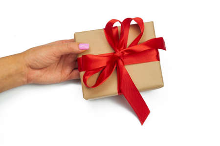 the girl is holding a gift box in her hand a surprise present with a tied red bow for St. valentine's day and birthday on a white background Stockfoto