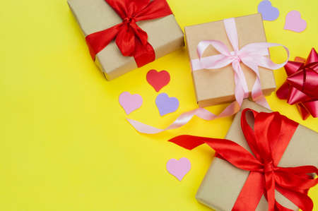 beautiful decor gift boxes surprise tied bows and ribbons with hearts on a yellow background for Valentine's Day