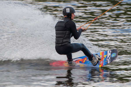 Kiev Ukraine - May 14, 2021, a guy, a man, an athlete rides and trains on the water as a sport Wakeboarding in the recreation area x - park