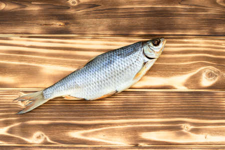 One dry roach fish lies on a wooden table view from above.