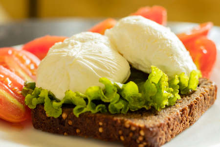 poached eggs on black bread toast with tomats breakfast