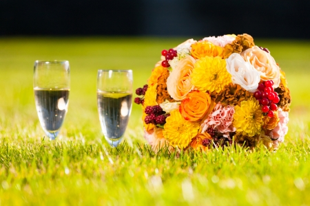 bouquet of beautiful flowers and two glasses on a holiday Stock Photo