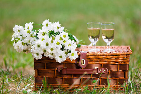 two glasses of white wine and a bouquet of white flowers photo