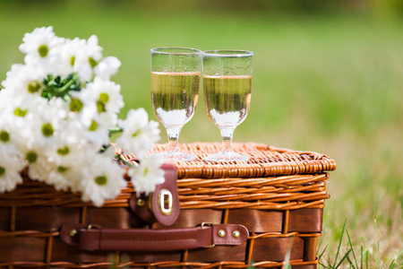 two glasses of white wine and a bouquet of white flowers Stock Photo