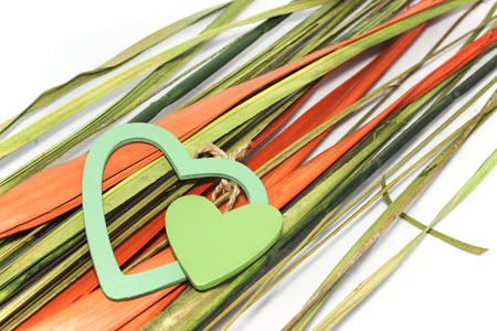 Two green hearts made from wood lay down on natural orange and green leafs photo