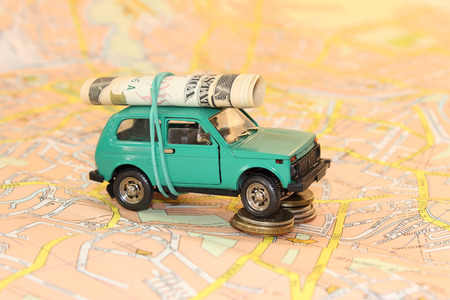 Green car with dollars and coins stay on the map background photo