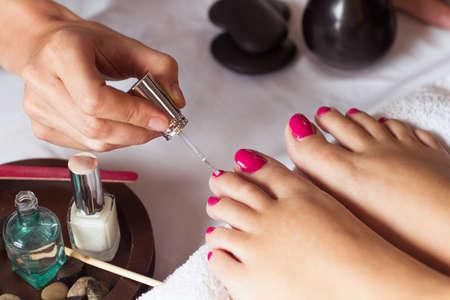 Vrouw in spijkersalon die pedicure ontvangen door schoonheidsspecialist. close-up van vrouwelijke hand die op witte handdoek rust