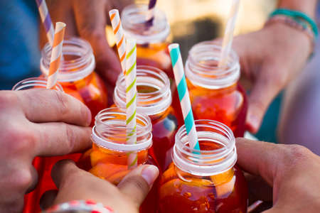 a straw: Picnic theme: group of friends holding drinks, toast , close-up Stock Photo