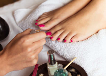 Woman in nail salon receiving pedicure by beautician. closeup of female hand resting on white towel Stock Photo - 47315503