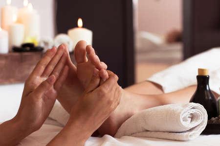 manos y pies: Masaje del pie humano en salón spa - Imagen del foco suave Foto de archivo