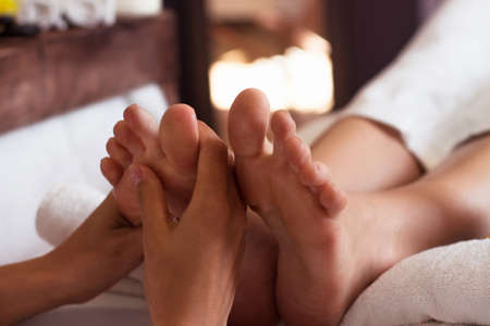 salon and spa: Massage of human foot in spa salon - Soft focus image