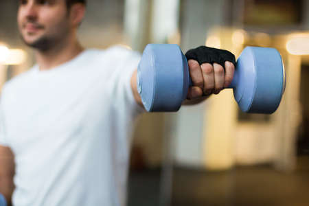 muscle boy: sport and recreation concept - sporty men hands with light blue dumbbells