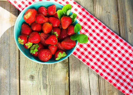 strawberry baskets: Spring fruits, strawberries in a paper bag on an old wooden background. Stock Photo