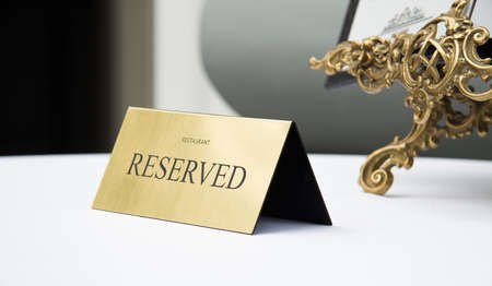 Reserved sign, reservation. On table. Beige