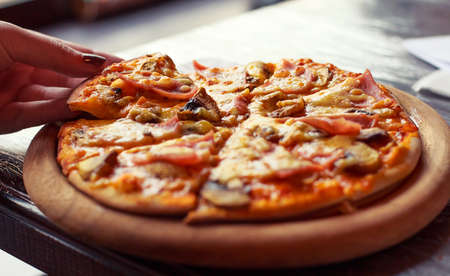 Fresh delicious home cooked pizza with steam on wood deck Standard-Bild