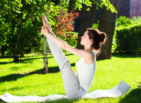 yoga meditation: Young beautiful woman doing yoga in the park in the morning Stock Photo