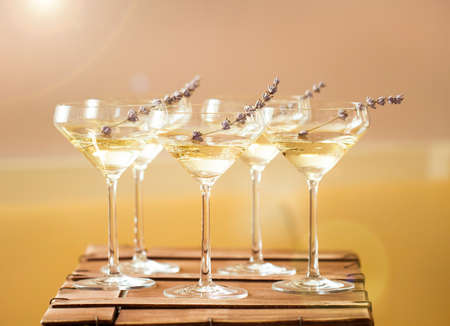 stemware: Glasses of with white champagne decorated with lavender on blurred background. DOF Stock Photo