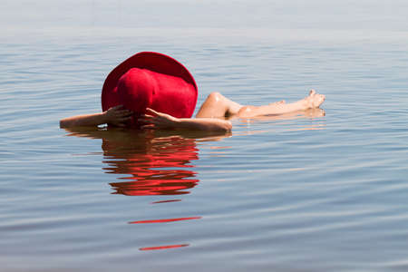 The lake with salt water. Baskunchak . Beautiful woman sunbathing in water Reklamní fotografie - 47516269