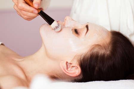 masaje facial: Mujer hermosa con la máscara facial en el salón de belleza. tratamiento de spa Foto de archivo