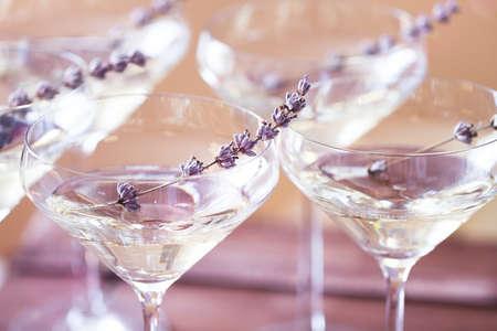 背景をぼかした写真のラベンダーで飾られた白のシャンパンのグラス。被写し界深度