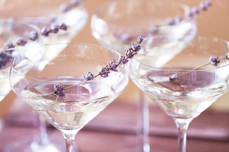 Glasses of with white champagne decorated with lavender on blurred background. DOF Stock Photo