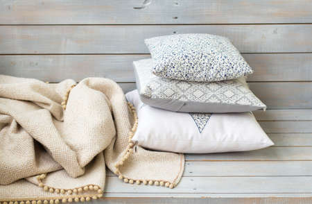 Cushions and plaid on the white wooden background closeup.