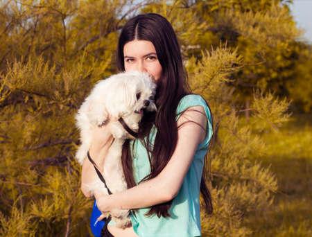 perro asustado: Hermosa morena con un perro joven disfrutando de un hermoso día al aire libre Foto de archivo