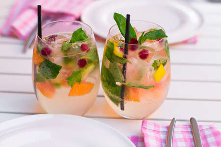 jag: Lemonade . A refreshing summer drink with berries, orange, lime, basil in a glass on a wooden table