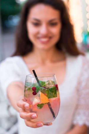 jovenes tomando alcohol: hermosa mujer sonriente beber baya limonada fría, en un café del verano Foto de archivo